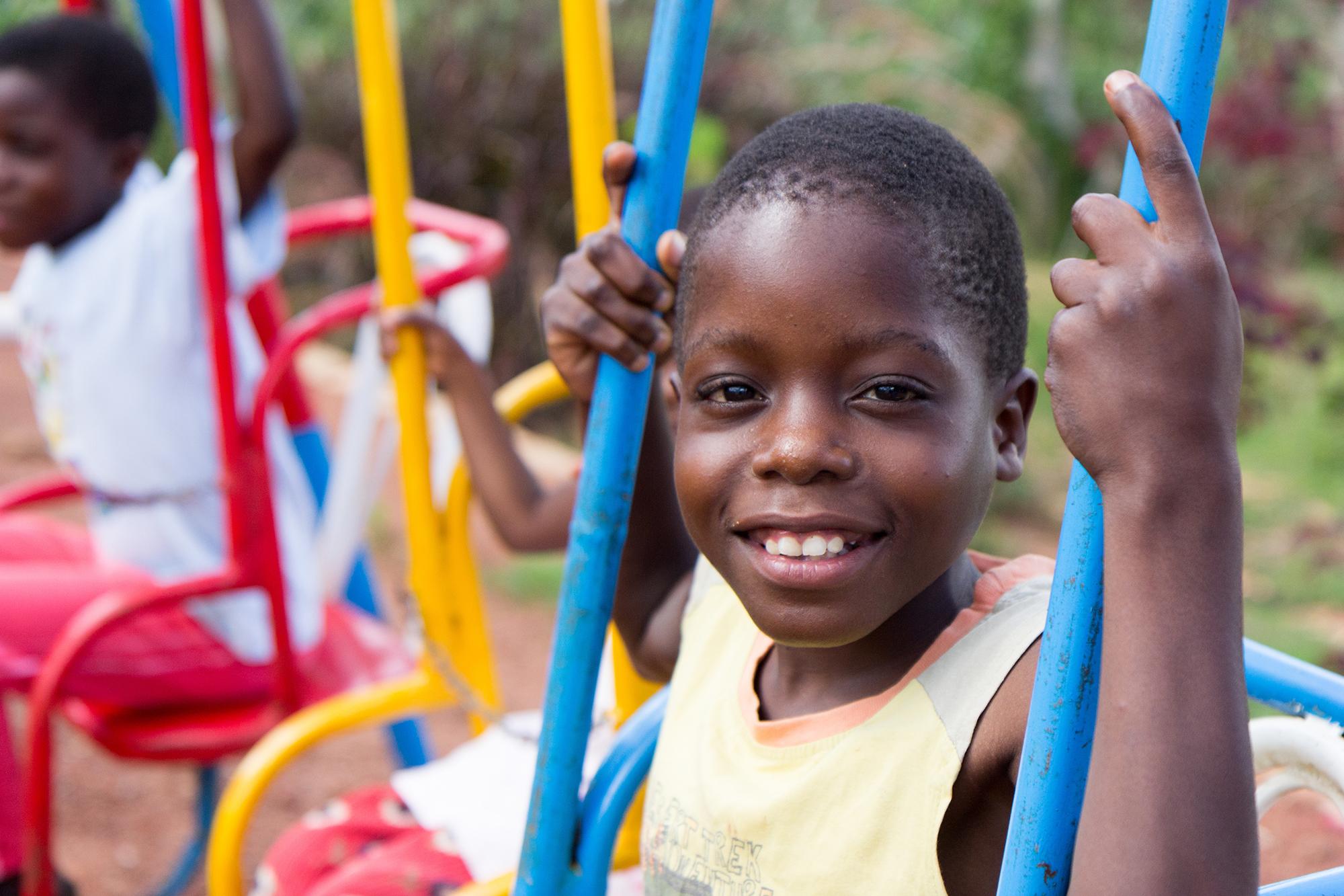 Ugandan boy swinging on a colorful swing